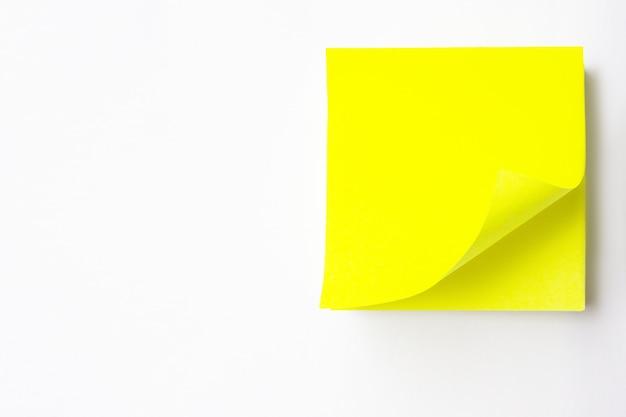 Nahaufnahme eines gelben leeren aufklebers ein weißer hintergrund. leere gelbe anmerkung mit schwarzem pin auf weißem gelbem hintergrund. leere gelbe haftnotiz
