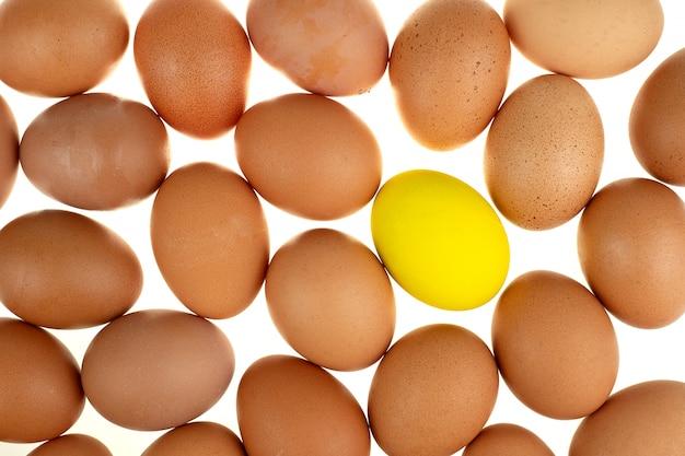 Nahaufnahme eines gelben osterei-huhns, umgeben von frischen eiern der natur