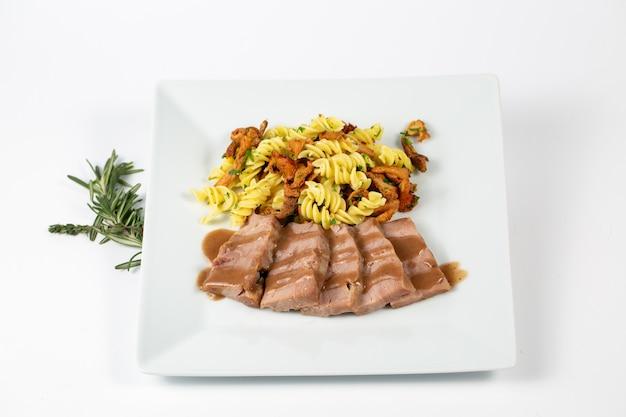 Nahaufnahme eines gerichts mit pastasauce und fleisch