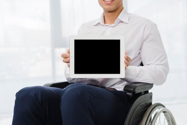 Nahaufnahme eines geschäftsmannes, der auf dem rollstuhl zeigt digitale tablette mit schwarzem bildschirm sitzt