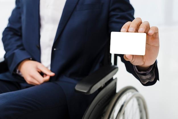 Nahaufnahme eines geschäftsmannes, der auf dem rollstuhl zeigt weiße visitenkarte sitzt