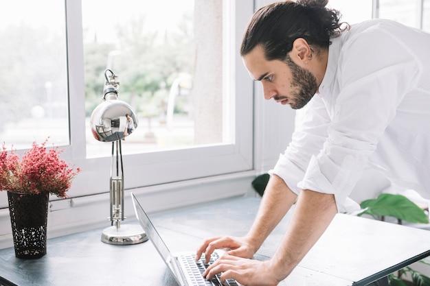 Nahaufnahme eines geschäftsmannes, der auf laptop über dem schreibtisch nahe dem fenster schreibt