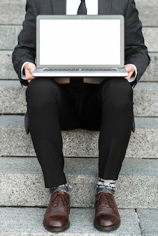 Nahaufnahme eines geschäftsmannes, der auf treppenhäusern mit einem offenen laptop über seinem schoss sitzt