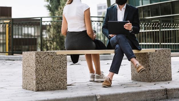 Nahaufnahme eines geschäftsmannes, der die digitale tablette sitzt mit seinem kollegen auf bank hält