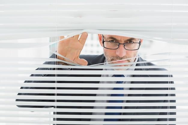 Nahaufnahme eines geschäftsmannes, der durch vorhänge im büro späht