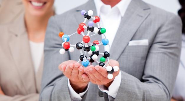 Nahaufnahme eines geschäftsmannes, der ein molekül anhält