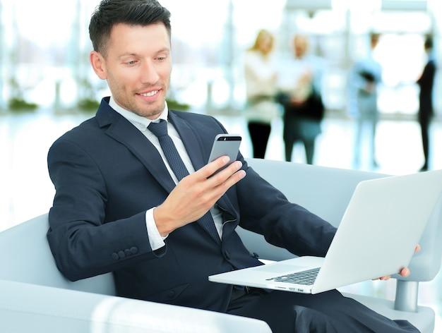 Nahaufnahme eines geschäftsmannes, der in einem stuhl mit ihrem smartphone sitzt und am laptop in der lobby der bank arbeitet.