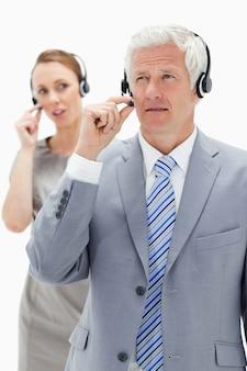 Nahaufnahme eines geschäftsmannes des weißen haares mit einer frau, die im hintergrund beim tragen eines kopfhörers spricht