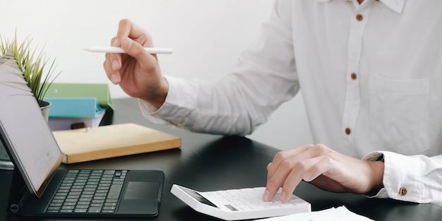 Nahaufnahme eines geschäftsmannes mit taschenrechner und laptop, um mathematische finanzen auf einem holzschreibtisch im büro zu erledigen?