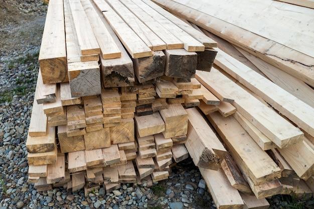 Nahaufnahme eines gestapelten stapels von natürlichen braunen, unebenen, rauen holzbrettern, die von heller sonne beleuchtet werden. industrieholz für zimmerei, bau, reparatur und möbel, bauholz.