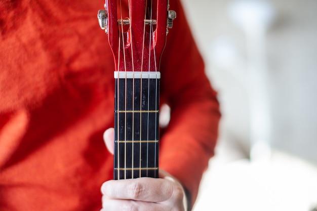 Nahaufnahme eines gitarristen oder einer person, die lernt, eine akustische gitarre zu spielen. zuhause lernen, ein musikinstrument zu spielen