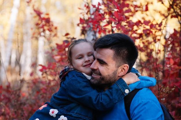 Nahaufnahme eines glücklichen familienporträts glücklicher lächelnder vater mit dunklem haar hält seine kleine tochter in blau ...