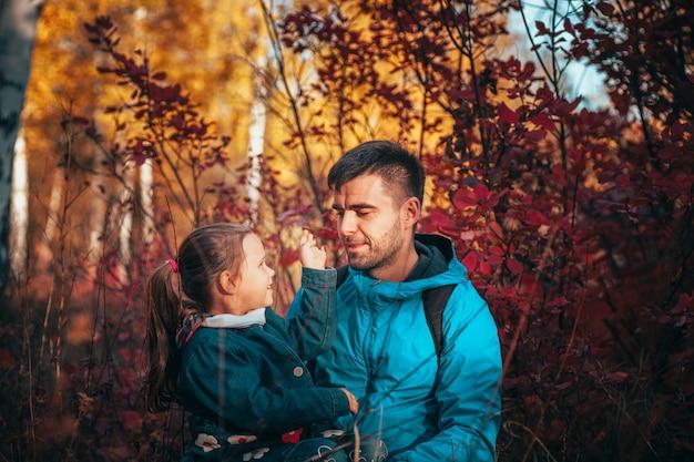 Nahaufnahme eines glücklichen familienporträts mit dunklen haaren, der seine kleine tochter in blauer jacke im herbst ansieht.