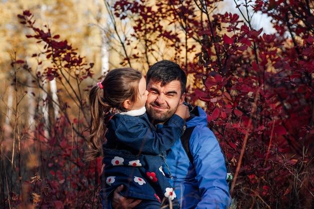 Nahaufnahme eines glücklichen familienporträts, süße kleine tochter, die ihren vater in blauer jacke im herbstwald küsst ...