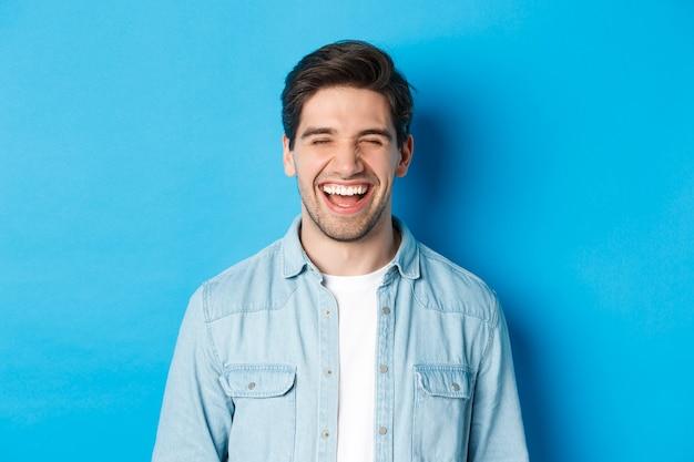 Nahaufnahme eines glücklichen jungen bärtigen mannes in freizeitkleidung, der lacht und sich freudig fühlt und auf blauem hintergrund steht.