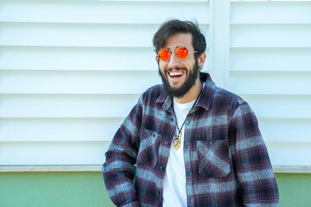 Nahaufnahme eines glücklichen jungen spaniers, der ein kariertes hemd an einer wand trägt