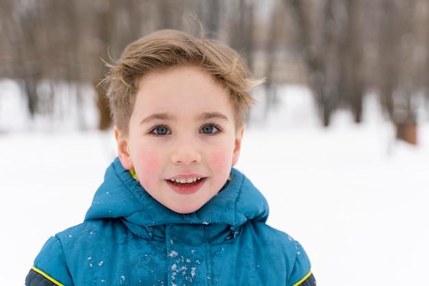 Nahaufnahme eines glücklichen kindes, das im schnee spielt