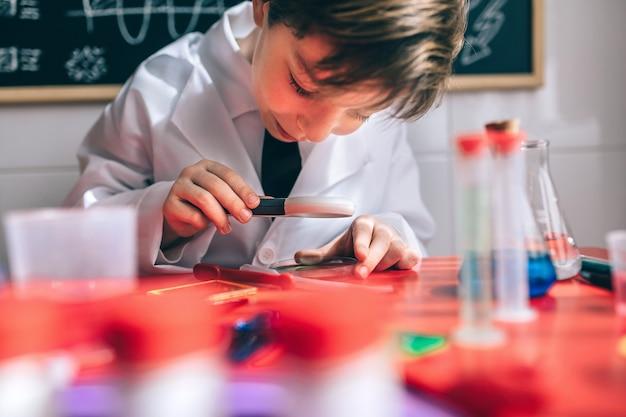 Nahaufnahme eines glücklichen kleinen wissenschaftlers, der chemische flüssigkeit mit lupe gegen die gezeichnete tafel sieht
