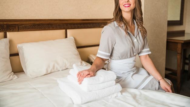 Nahaufnahme eines glücklichen stubenmädchens, das auf bett mit gestapeltem weichem gefaltetem tuch im hotelschlafzimmer sitzt