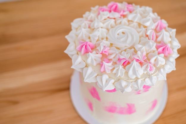 Nahaufnahme eines großen kuchens mit rosa sahne und baiser. eine zarte geburtstagstorte für ein mädchen. hochzeitstorte.