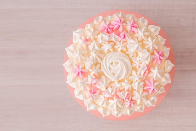 Nahaufnahme eines großen kuchens mit rosa sahne und baiser. zarte geburtstagstorte für ein mädchen auf einem hölzernen hintergrund. der blick von oben.