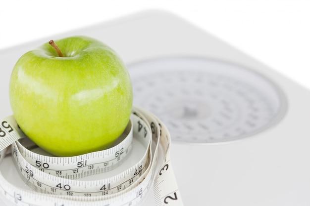 Nahaufnahme eines grünen apfels kreiste mit einem maßband ein und wiegt-wiegt