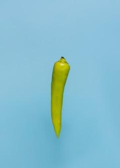 Nahaufnahme eines grünen paprikapfeffers auf blauer oberfläche