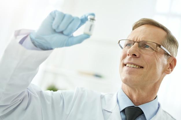 Nahaufnahme eines gutaussehenden arztes in sterilen handschuhen, der medikamente betrachtet und lächelt