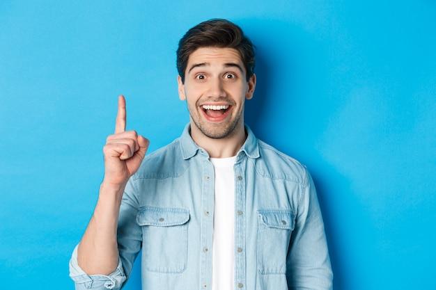 Nahaufnahme eines gutaussehenden bärtigen kerls, der lächelt, finger nummer eins zeigt und auf blauem hintergrund steht