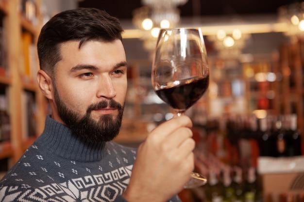 Nahaufnahme eines gutaussehenden bärtigen mannes, der rotwein in seinem glas untersucht und getränke im weingut probiert