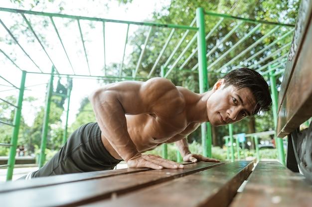 Nahaufnahme eines gutaussehenden mannes, der liegestütze macht, um brustmuskeln aufzubauen und gewicht zu verlieren, indem er im freien auf der bank im park trainiert