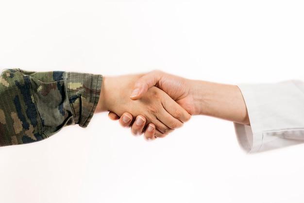 Nahaufnahme eines händedrucks eines soldaten und eines arztes
