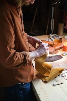 Nahaufnahme eines handwerkers, der ledertextilien in den händen hält und produkte in der werkstatt herstellt