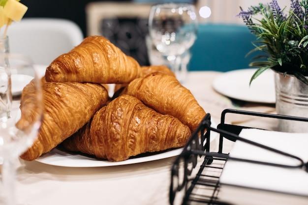 Nahaufnahme eines haufens frisch gebackener croissants auf einem teller auf dem tisch Premium Fotos