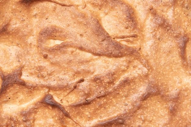 Nahaufnahme eines hausgemachten süßen kuchens draufsicht, beschaffenheit der gebackenen geschlagenen eiweißkruste.