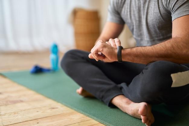 Nahaufnahme eines herrn, der auf einer yogamatte sitzt und eine moderne uhr auf seiner hand betrachtet