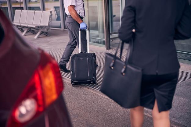 Nahaufnahme eines herrn, der reisekoffer trägt, während eine elegante frau hinter ihm geht?
