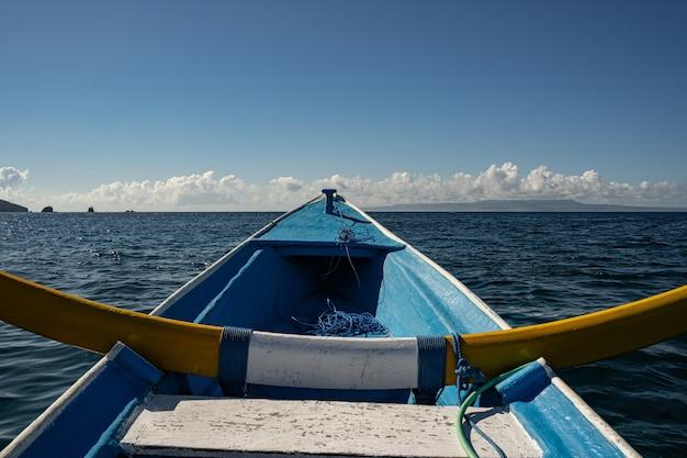 Nahaufnahme eines hölzernen fischerbootes, das auf wasser und blauem himmel im hintergrund schwimmt stockfoto