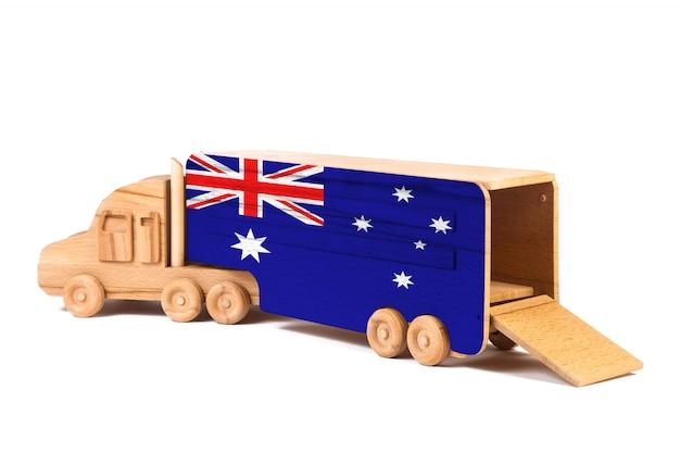 Nahaufnahme eines hölzernen spielzeuglastwagens mit einer gemalten staatsflagge australien. das konzept des exports und imports, des transports, der nationalen lieferung von waren