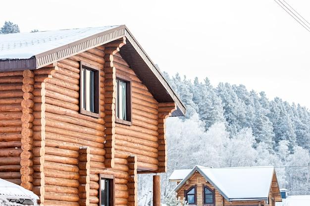Nahaufnahme eines holzhauses, das dach ist mit schnee bedeckt, rauch kommt aus dem schornstein