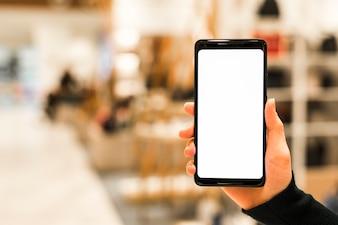 Nahaufnahme eines intelligenten Telefons der Person, das weißen Bildschirm gegen unscharfen Hintergrund zeigt