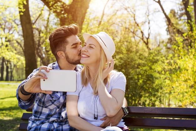 Nahaufnahme eines jungen attraktiven paares, das ein glückliches selfie in einem park macht