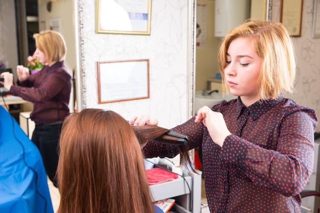 Nahaufnahme eines jungen blonden stylisten mit bügeleisen auf langem haar einer brünetten kundin im salon mit verschwommener reflexion im großen spiegel im hintergrund