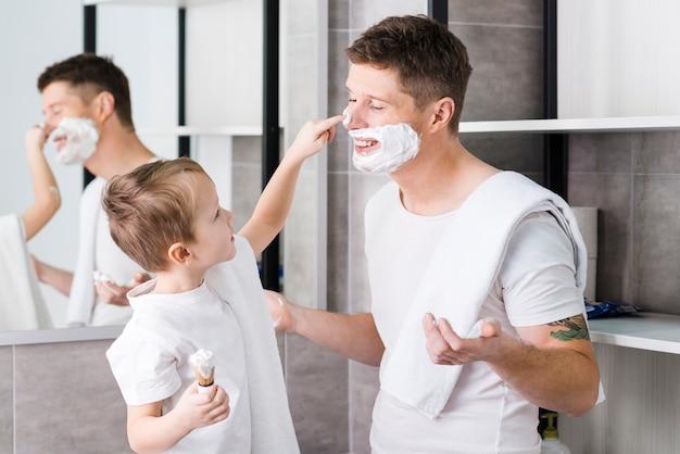 Nahaufnahme eines jungen, der schaum auf dem gesicht seines vaters im badezimmer rasierend zutrifft
