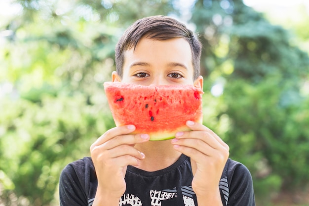 Nahaufnahme eines jungen, der wassermelonenscheibe über seinem mund hält