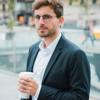 Nahaufnahme eines jungen geschäftsmannes, der die wegwerfkaffeetasse in der hand betrachtet kamera hält