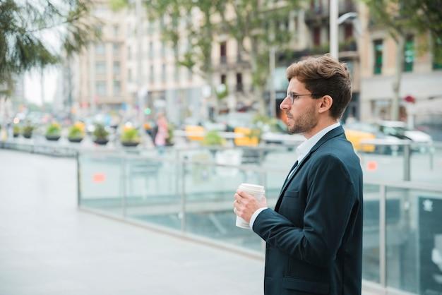 Nahaufnahme eines jungen geschäftsmannes, der in der hand die wegwerfkaffeetasse steht auf straße hält