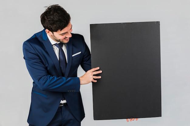 Nahaufnahme eines jungen geschäftsmannes, der leeres schwarzes plakat gegen grauen hintergrund hält