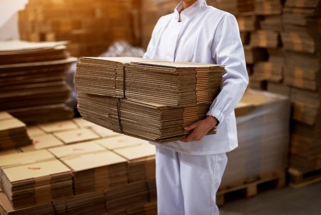 Nahaufnahme eines jungen hart arbeitenden angestellten in den sterilen tüchern, die den stapel der gefalteten kisten des braunen kartons vom fabrikladeraum tragen.