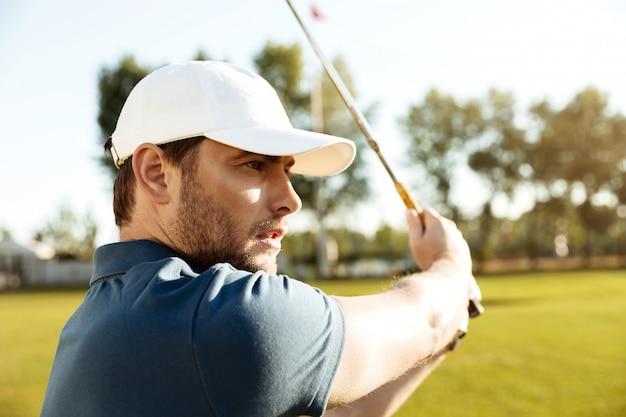 Nahaufnahme eines jungen männlichen golfspielers, der einen fairway-schuss trifft